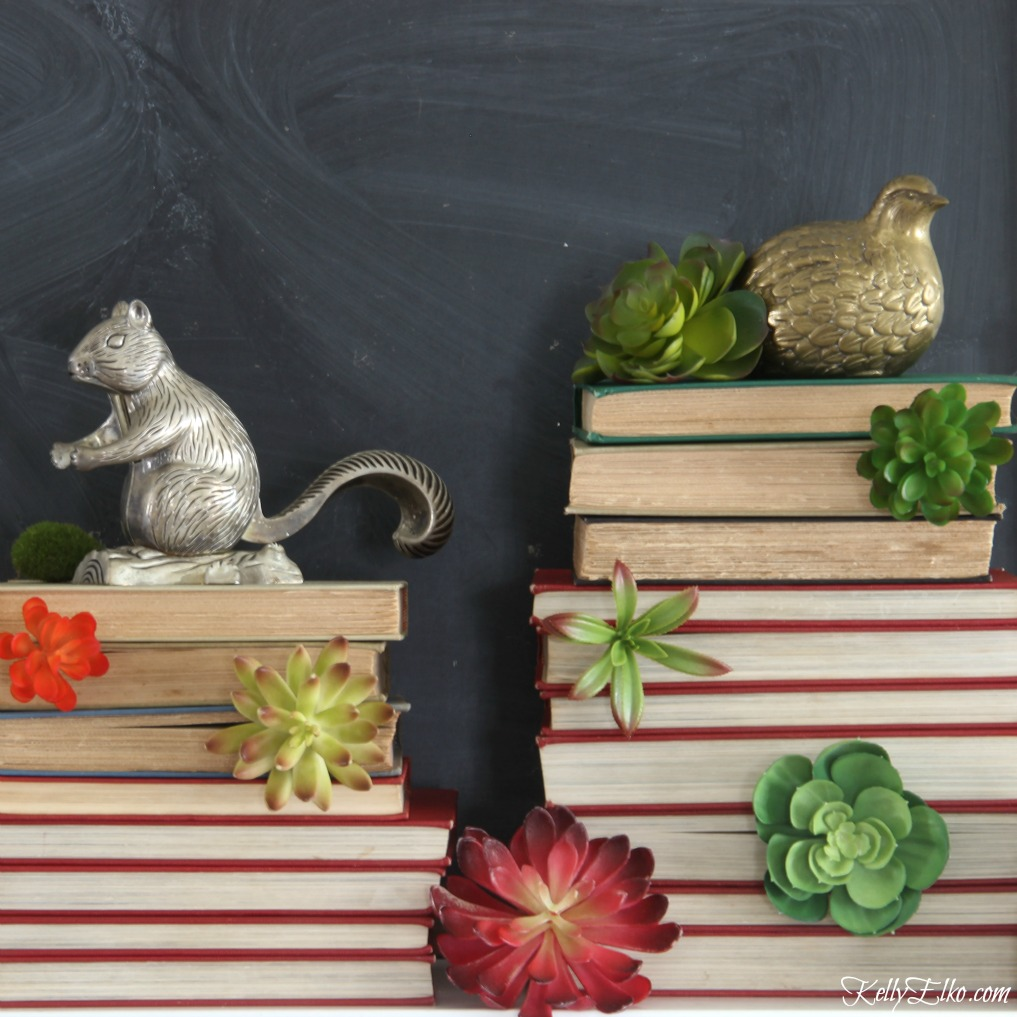 LOVE this mantel of old stacked books succulent towers and vintage brass and silver animals kellyelko.com
