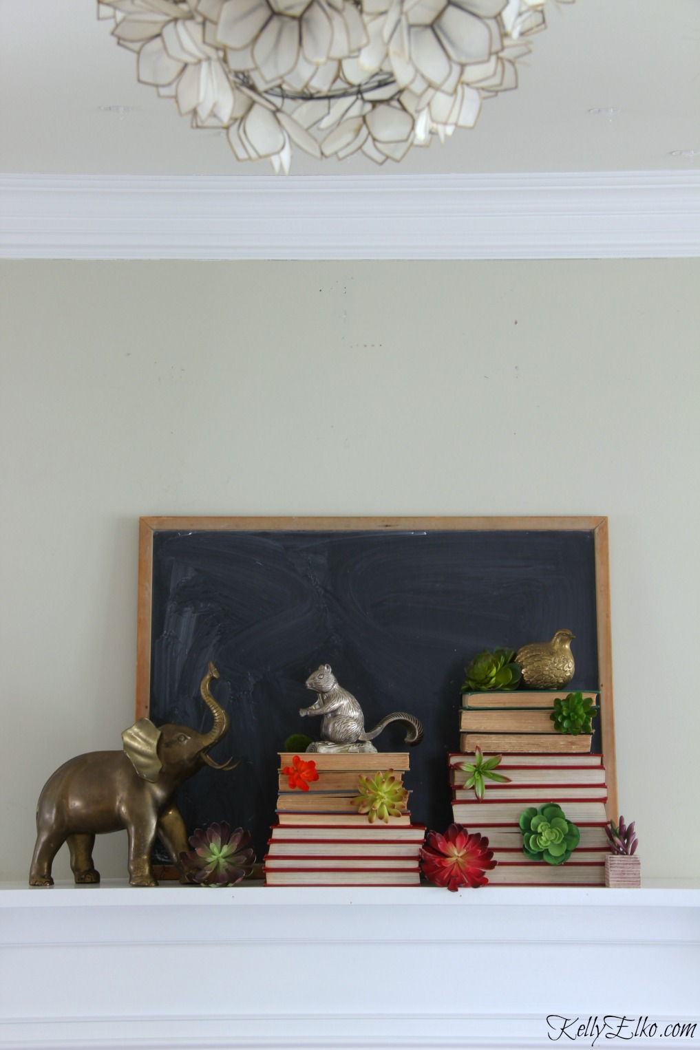 Vintage winter mantel - love the stacks of books with succulents and collection of brass animals kellyelko.com