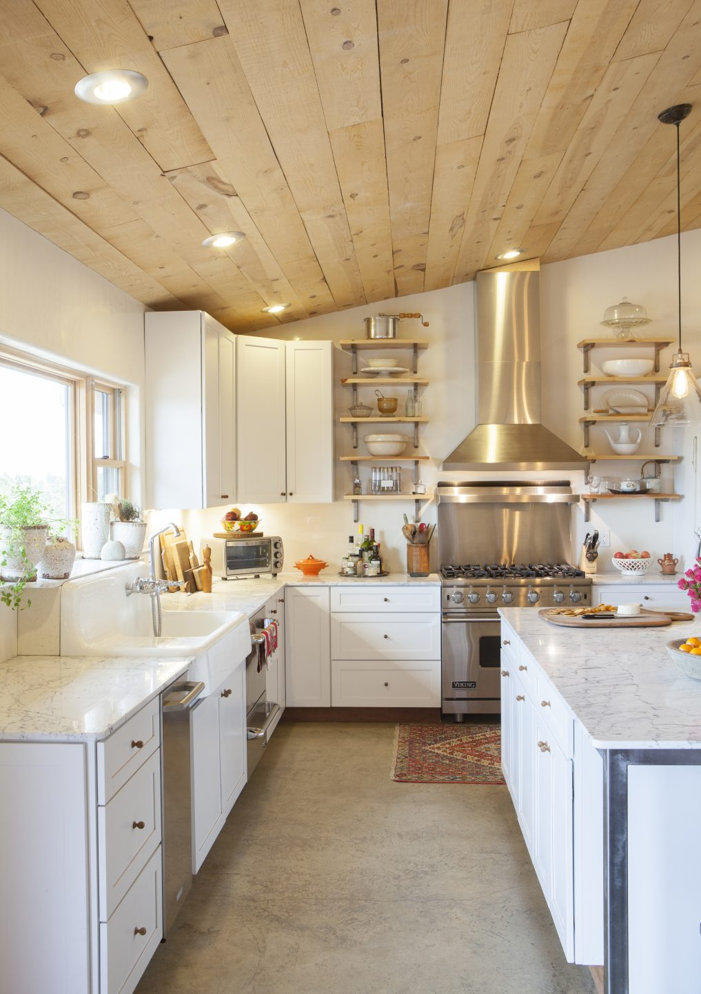 Love the hand hewn wood on the ceiling and the concrete floors of this kitchen