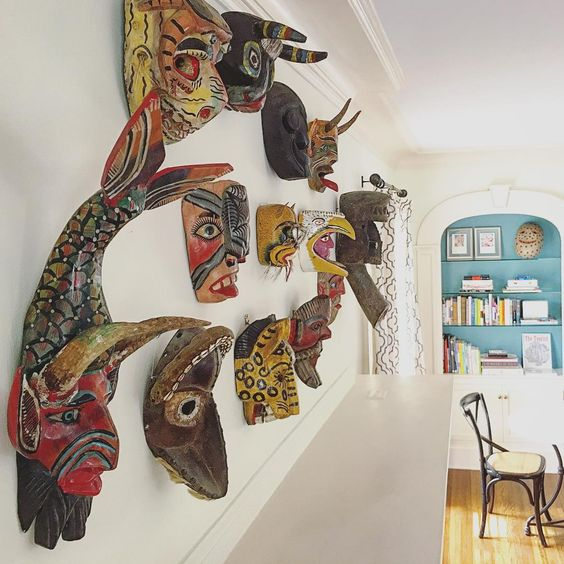A collection of antique African masks are a fun alternative to art over a mantel kellyelko.com