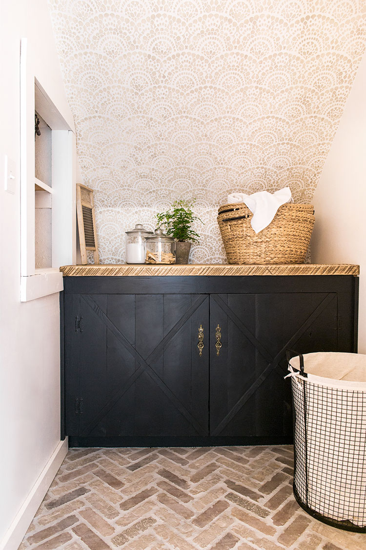 Black cabinets and herringbone brick floors