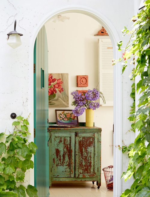 Teal arched front door opens into a colorful entry