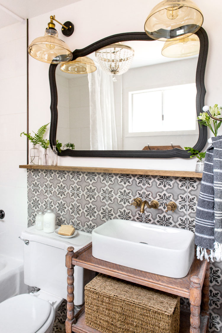 Vintage style lighting adds charm to this cottage bathroom with concrete tile