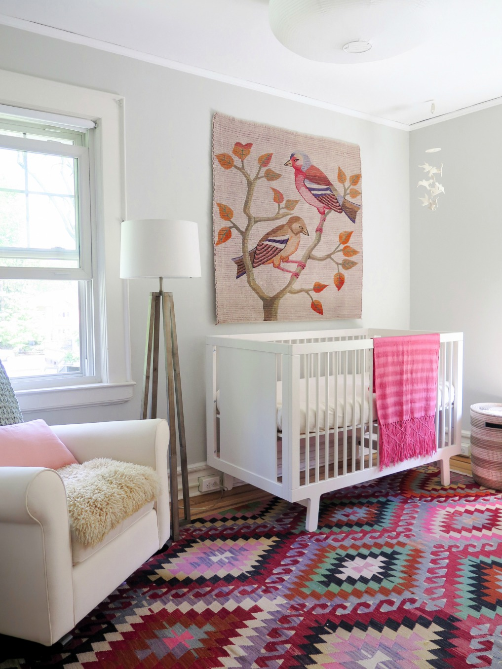 Pink nursery - love the vibrant rug and bird tapestry