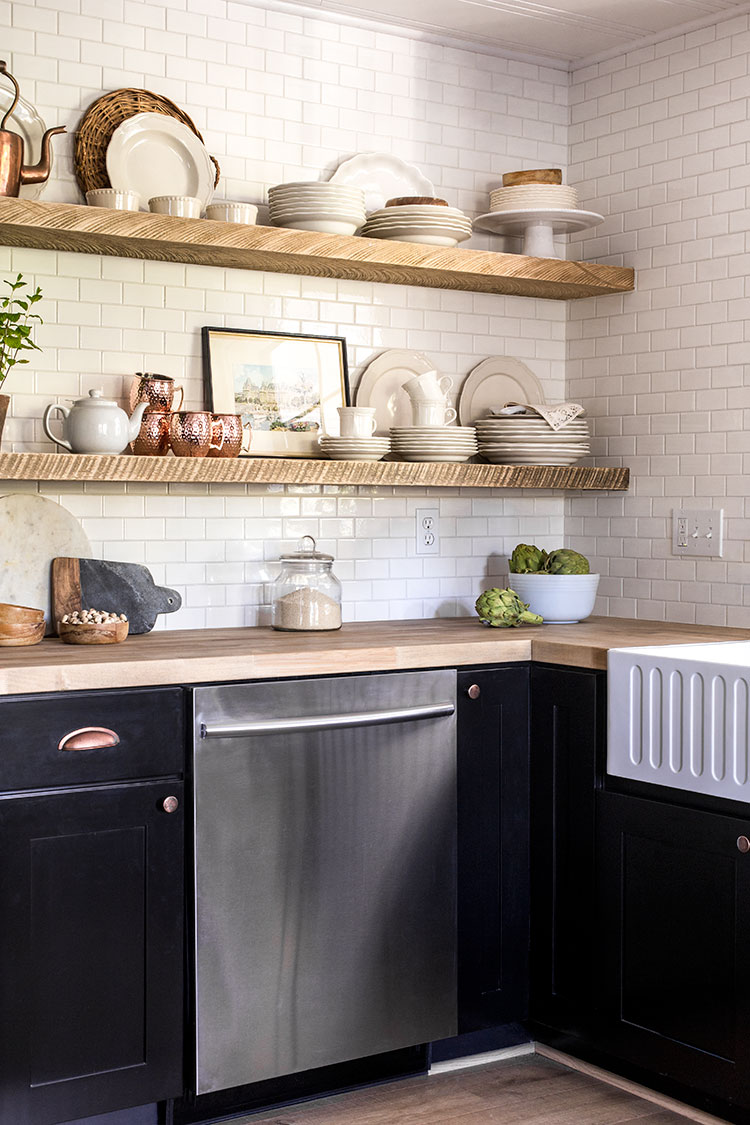 Rustic wood shelves add character to a white and black kitchen
