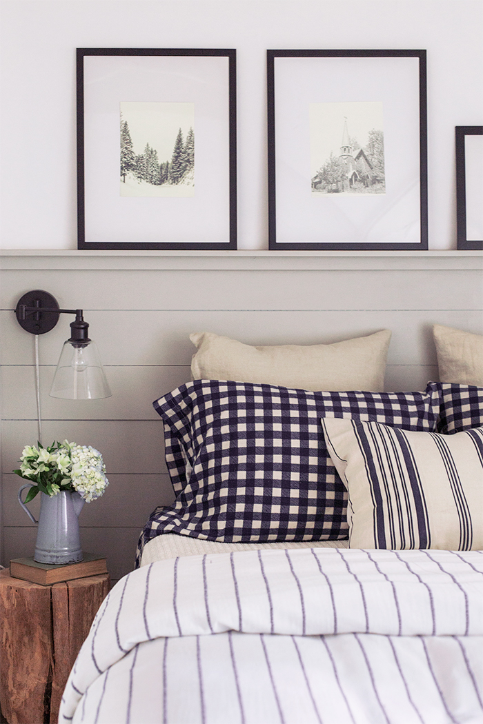 Shiplap walls and crisp striped bedding in this classic cottage bedroom