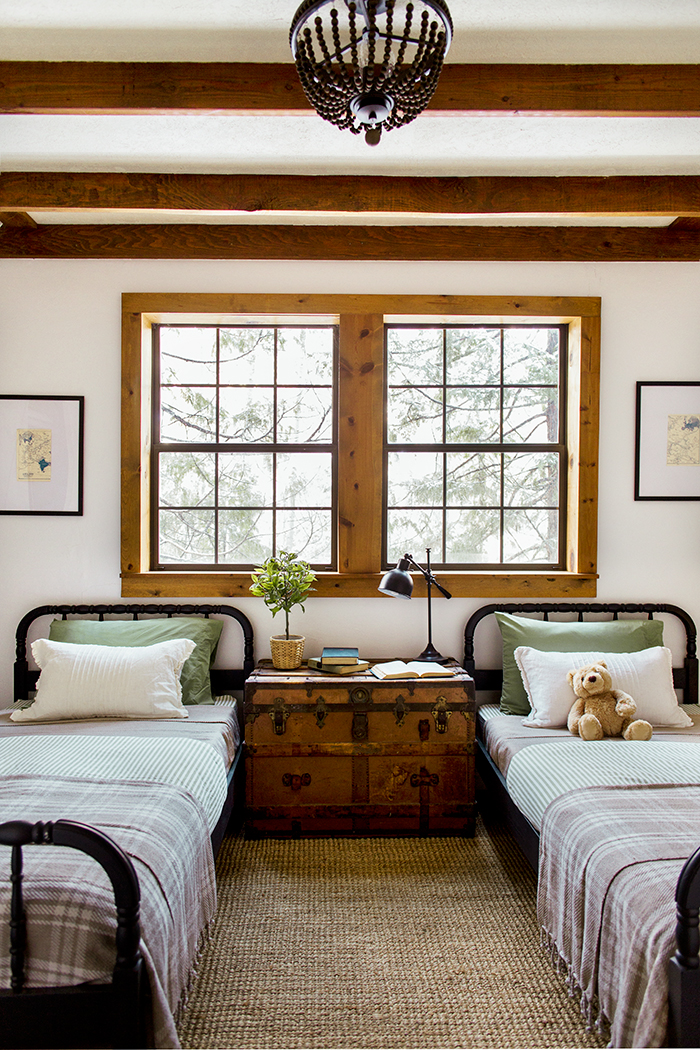 Twin beds in the kids room with an antique trunk nightstand