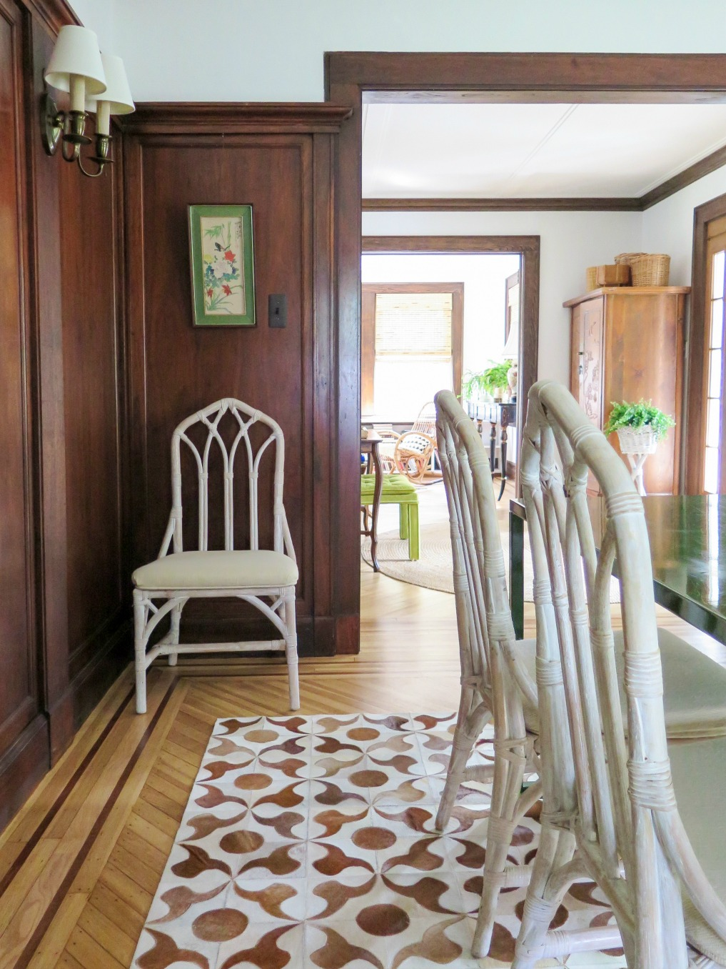 White bamboo chairs and a cowhide rug in the dining room of this 1920s home