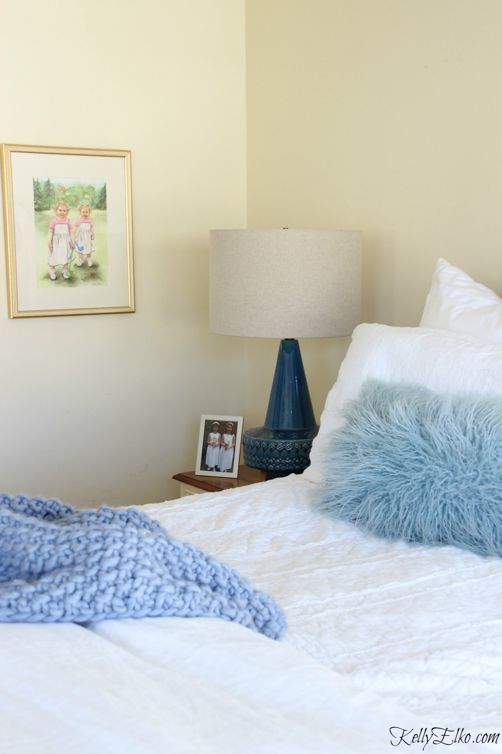 Neutral bedroom with pops of blue from lamp, throw and pillows kellyelko.com