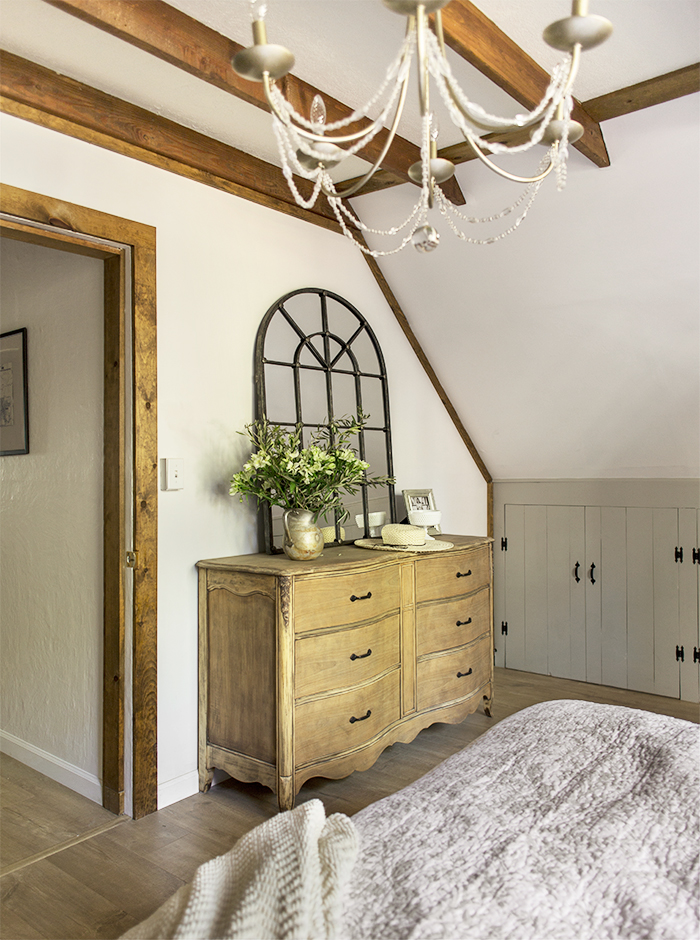 Rustic wood beams add character to a white bedroom
