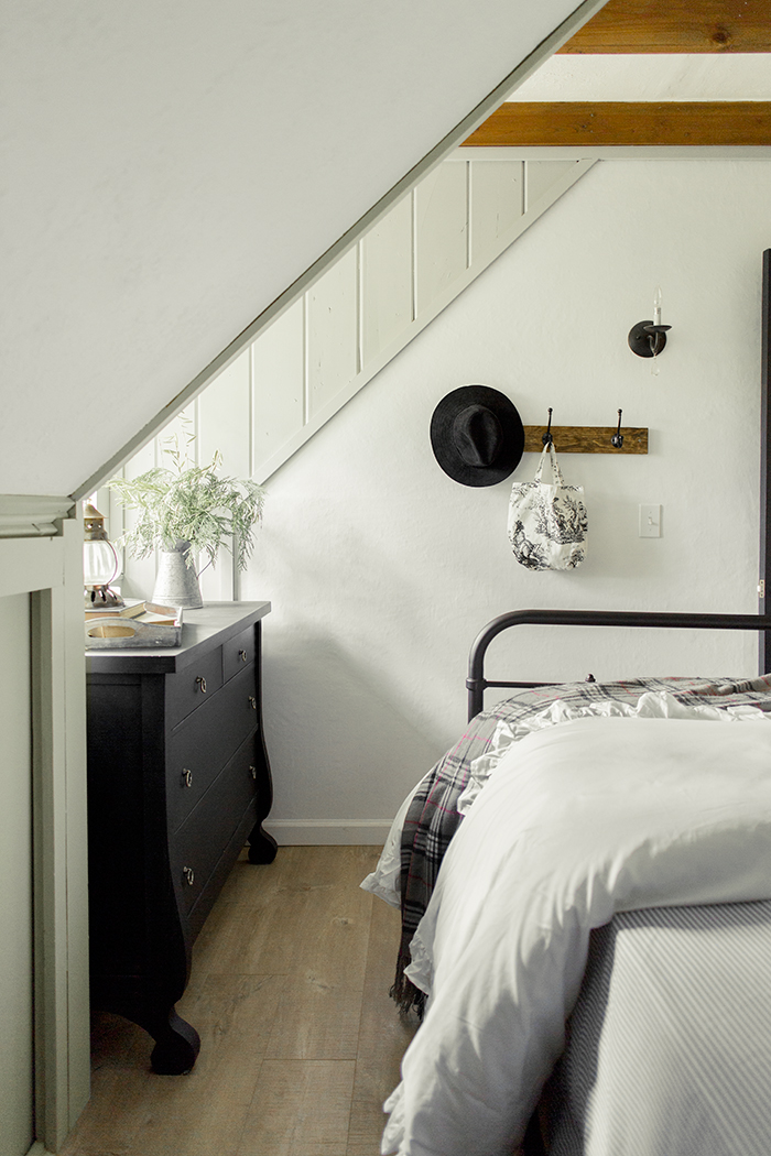 White and black bedroom with warm wood beams