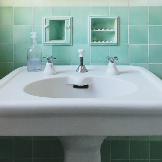 Antique green bathroom with original tile, soap holder and sink kellyelko.com