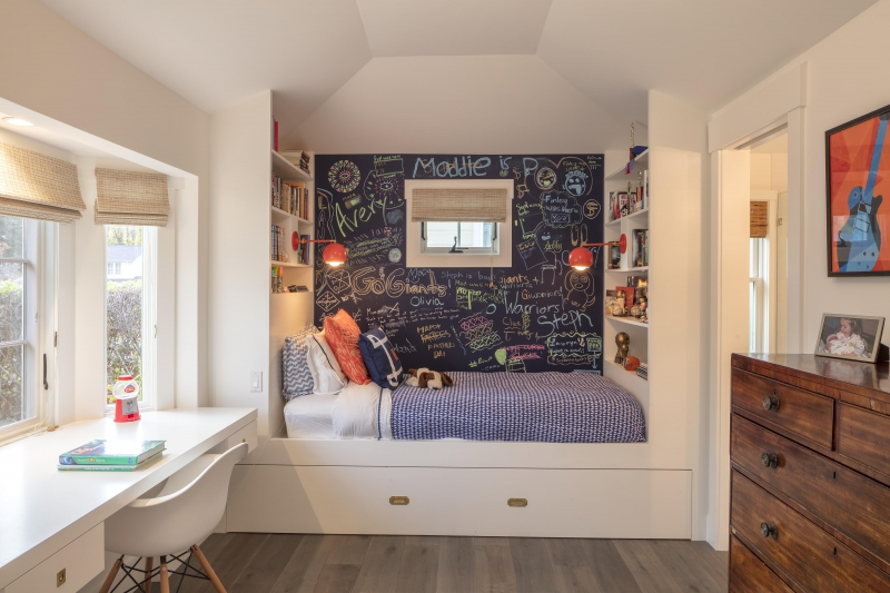 Kids bedroom with built in bed, bookshelves and desk maximize space