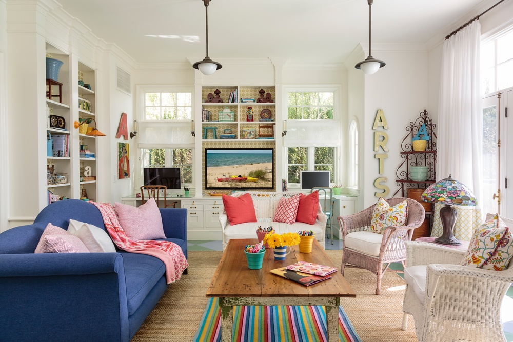 Colorful family room is grounded by white walls and neutral rug