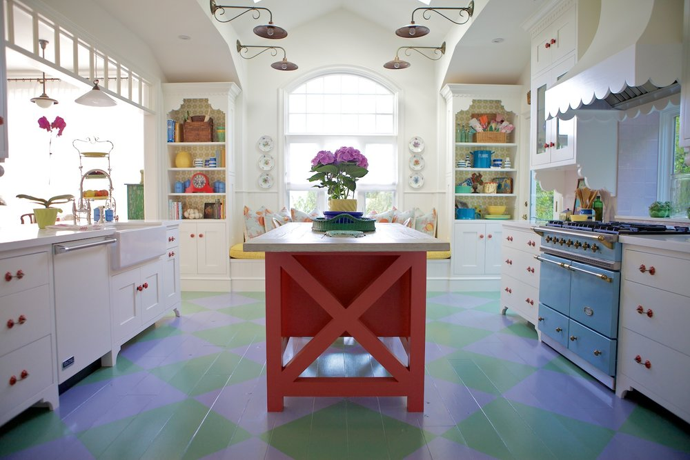 Colorful kitchen with painted wood floor, red island and blue stove