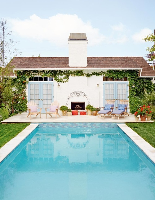 Stunning pool house with blue french doors and climbing vines