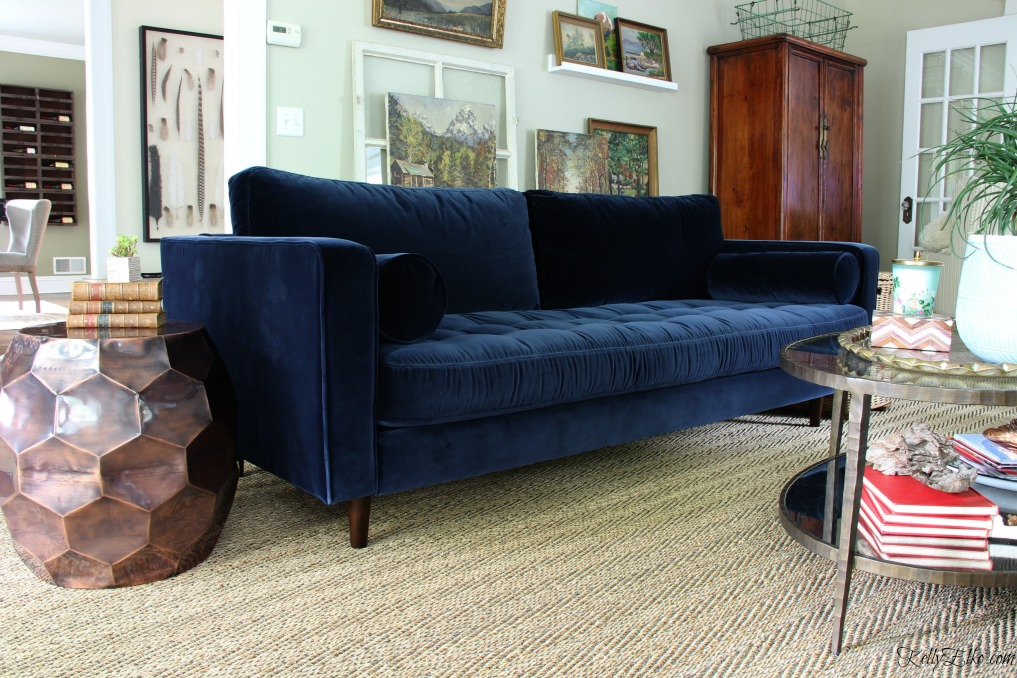 Mid century style blue velvet sofa - love this eclectic room with vintage landscape gallery wall kellyelko.com