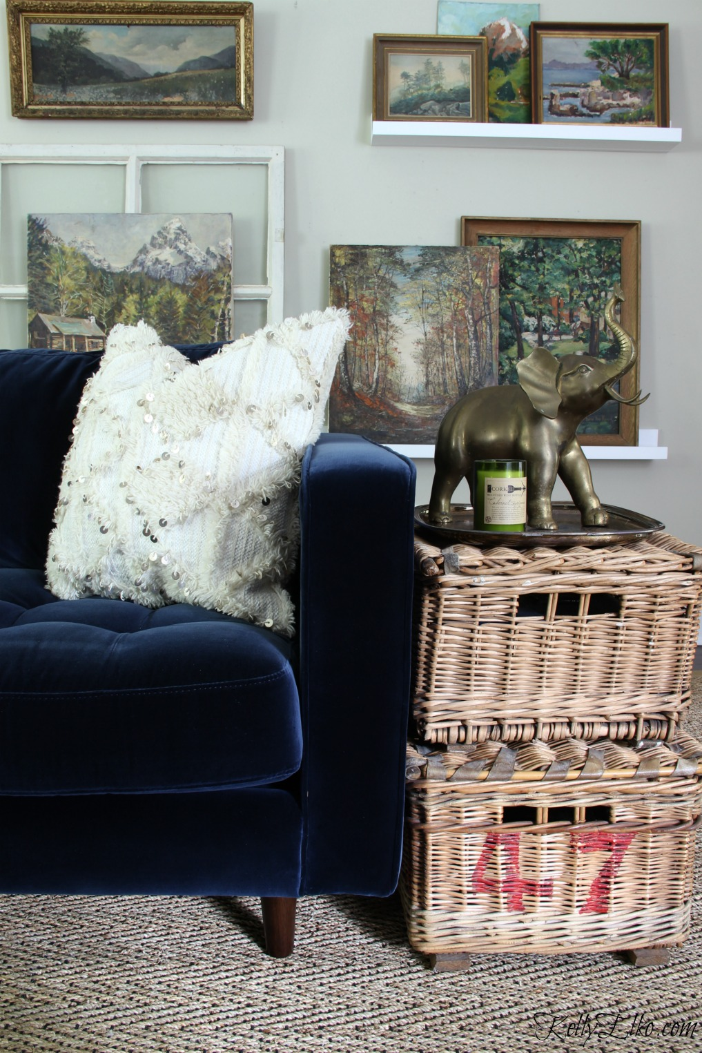Eclectic Mix - mid century modern style blue velvet sofa, seagrass rug, vintage landscape paintings and antique wicker baskets kellyelko.com