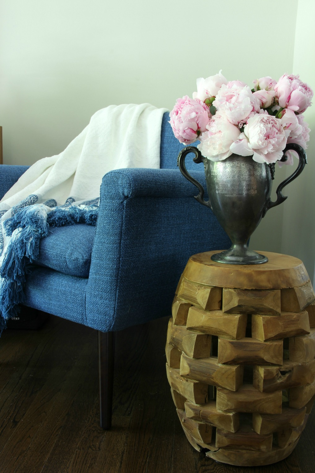 Cozy corner with blue mid chair, tassel throw and stunning bouquet of pink peonies kellyelko.com
