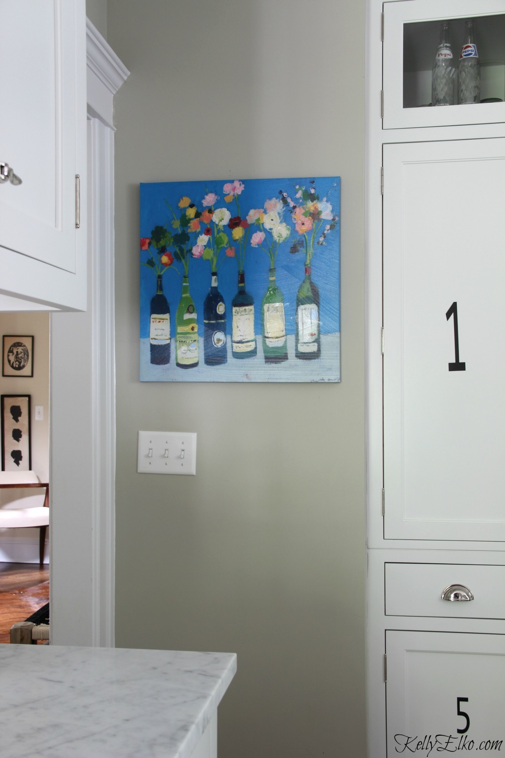 Colorful wine bottle flower art brings life to a white kitchen kellyelko.com