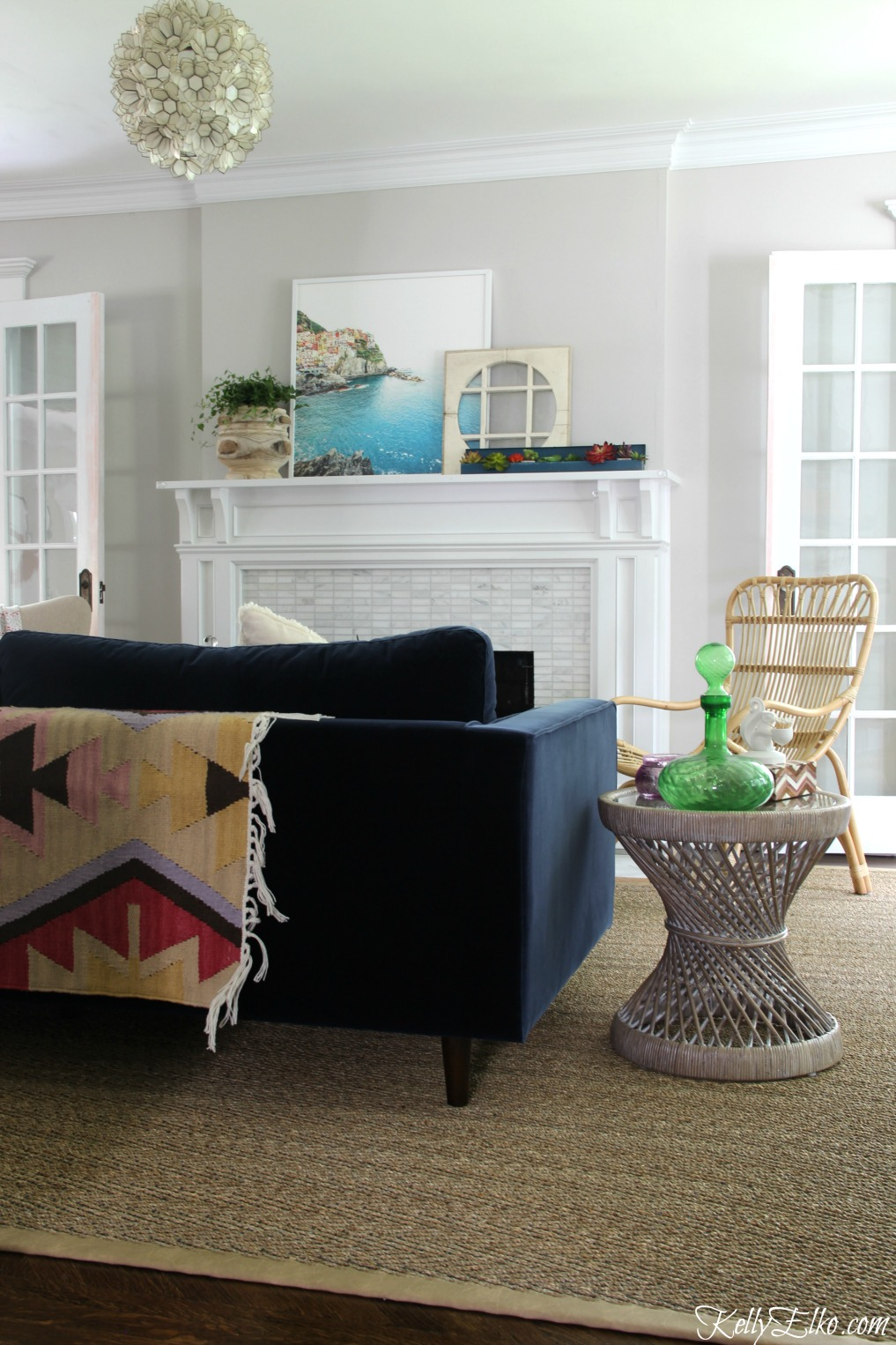 Colorful living room - love the blue velvet sofa and colorful rug draped over back and the capiz shell chandelier kellyelko.com