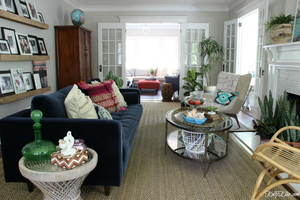 Colorful living room makeover - love the blue velvet sofa and colorful accents paired with rattan and sea grass for texture kellyelko.com
