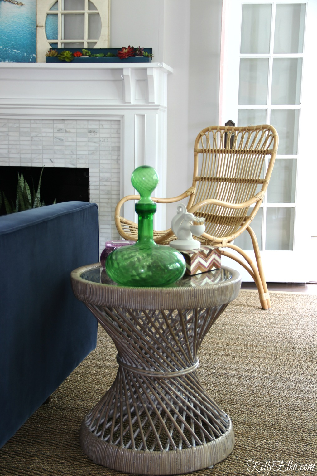 A rattan table and chair and seagrass rug add so much texture to this living room kellyelko.com