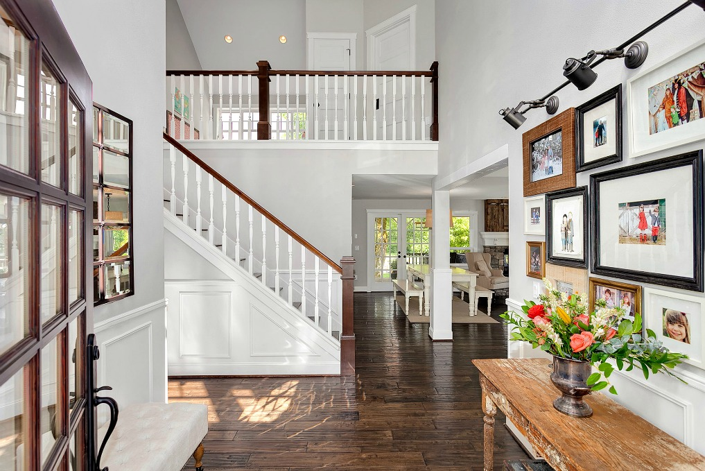 Love this foyer with dramatic staircase and family photo wall kellyelko.com