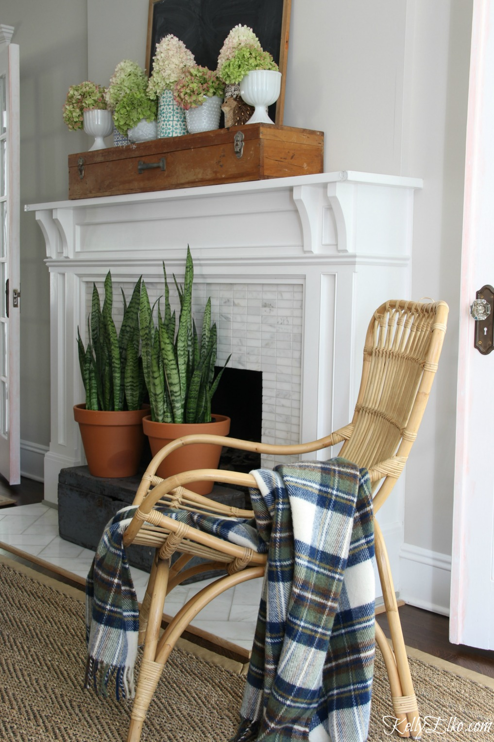 Love the boho feel of this living room with rattan chair, cozy wool throw and hydrangea filled mantel kellyelko.com