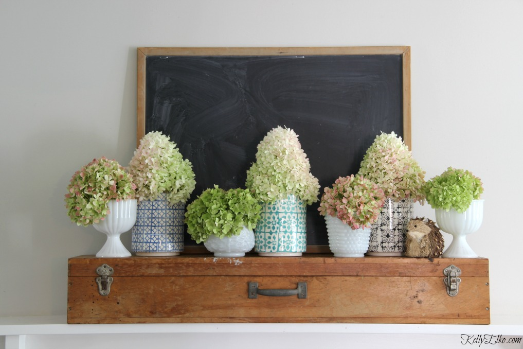 Beautiful mantel of hydrangeas in colorful vases mixed with vintage milk glass kellyelko.com