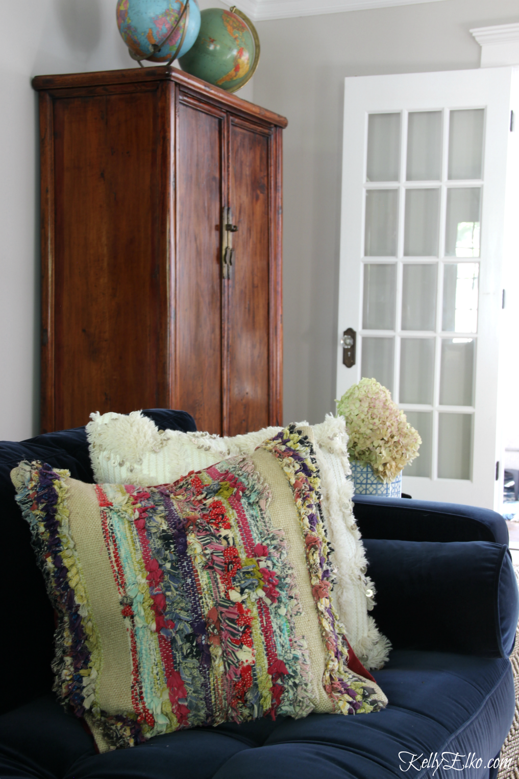 Colorful boho style pillows brighten up a navy blue sofa kellyelko.com