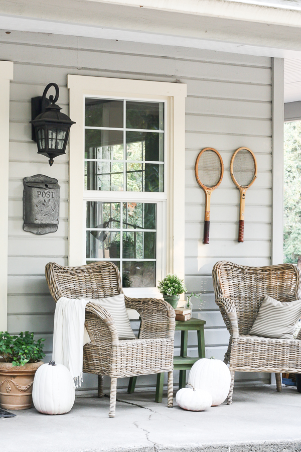 Farmhouse tour - love the wicker chairs and old tennis racquet art on the porch