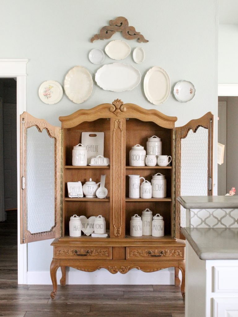 Farmhouse tour - love this antique cabinet displaying Rae Dunn collection
