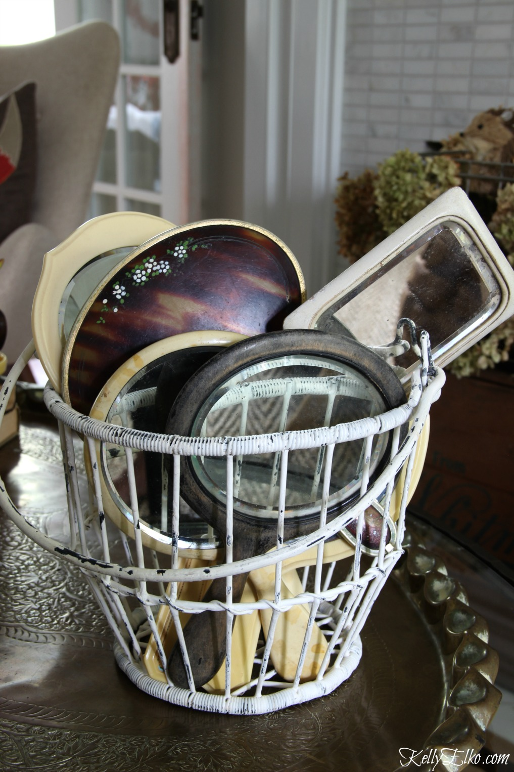 Collection of vintage hand mirrors displayed in a wire basket kellyelko.com