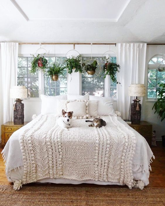 Boho bedroom with plant window treatment and chunky knit blanket