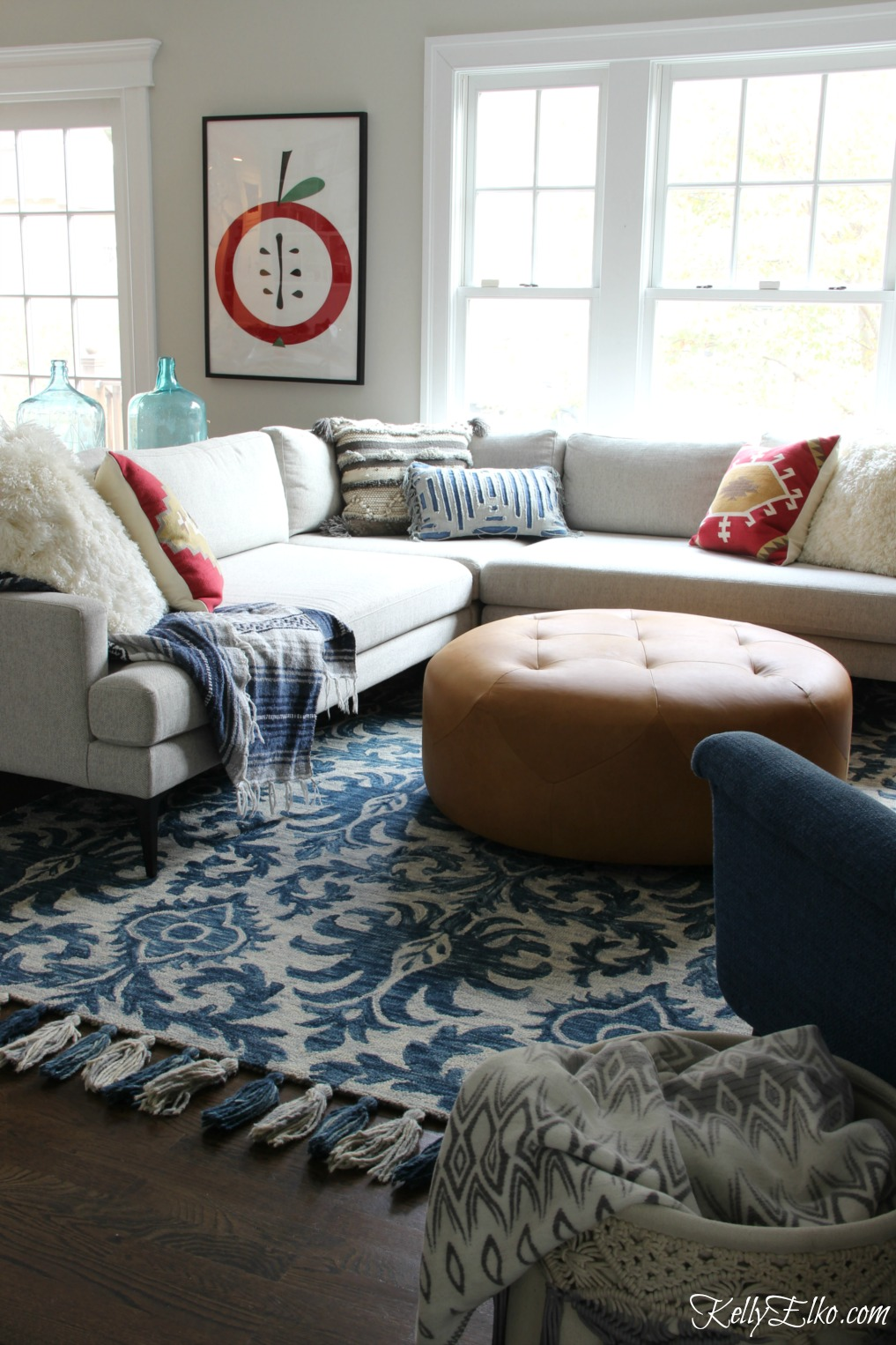 Cozy family room with sectional sofa, leather ottoman and blue tassel rug kellyelko.com