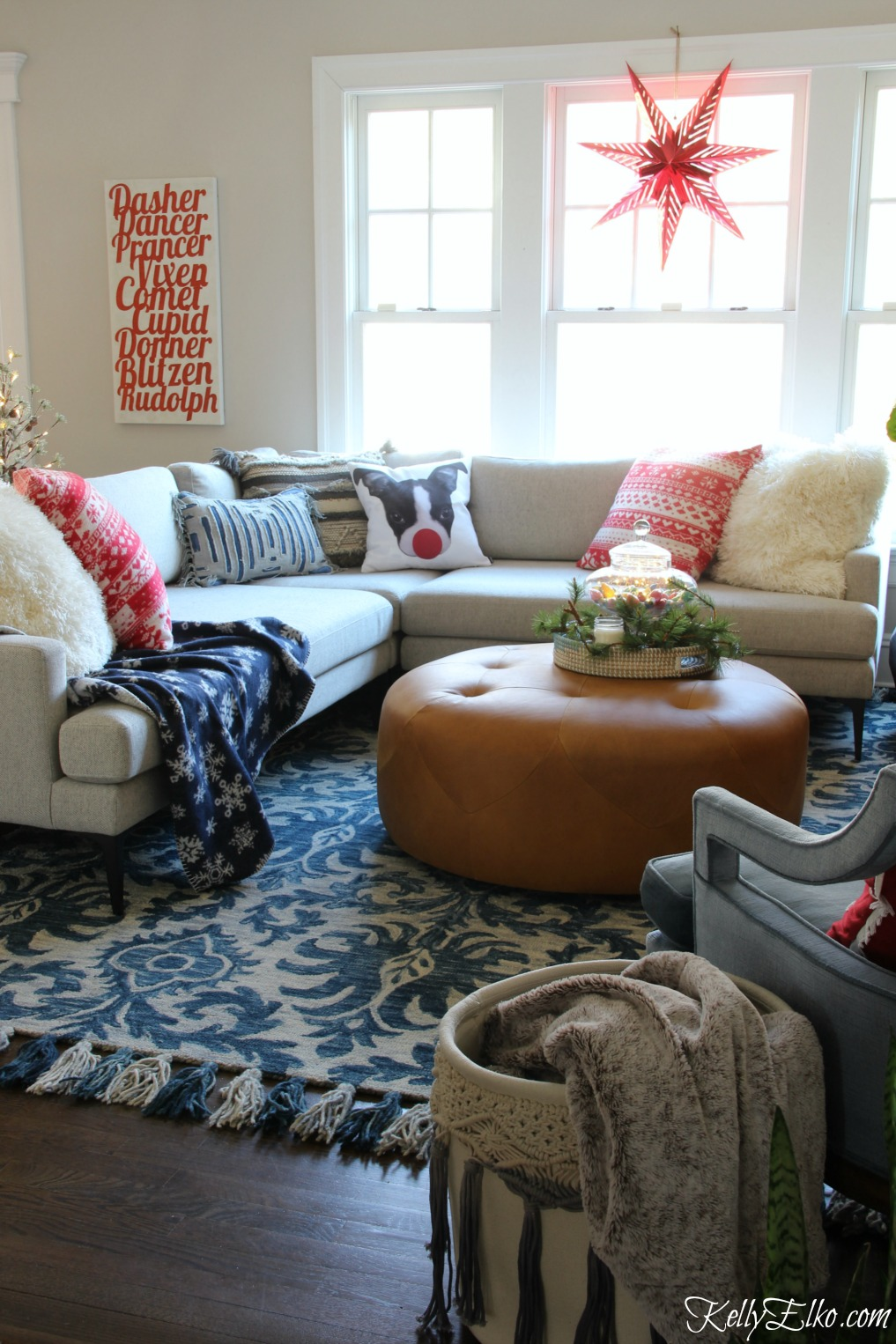 Christmas Home Tour - love this sectional sofa with fun pillows and the paper star in the window kellyelko.com
