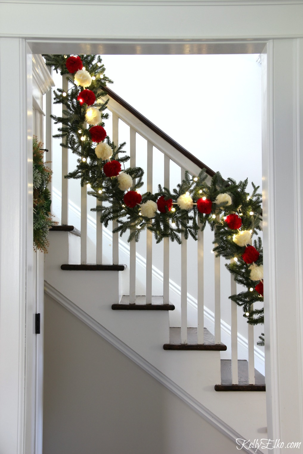 Christmas Home Tour - love this banister with pom pom garland kellyelko.com