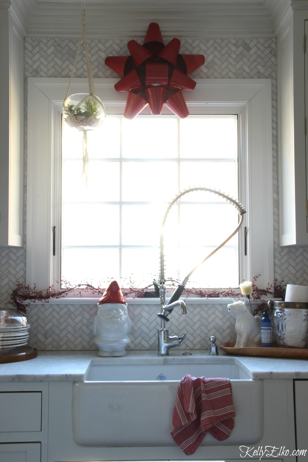 Christmas Kitchen - love the big red metal bow instead of a wreath kellyelko.com
