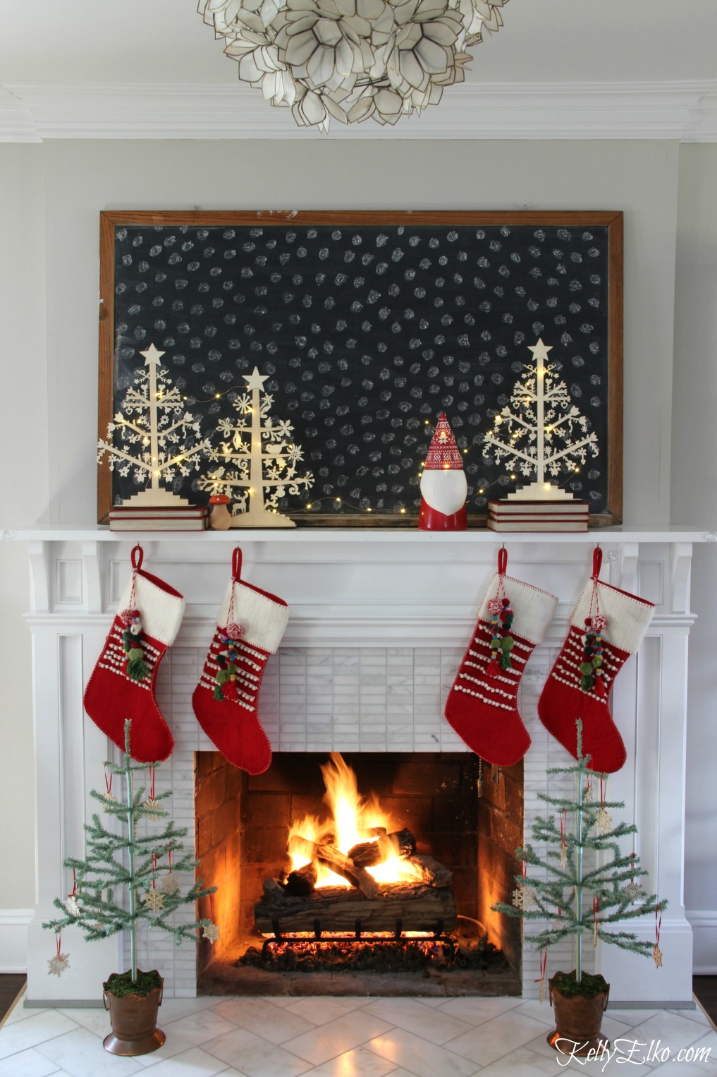 Christmas Home Tour - love this Scandinavian style mantel with huge chalkboard and pom pom stockings kellyelko.com