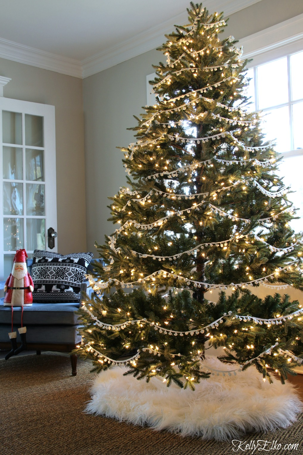 Christmas Home Tour - love this tree with pom pom garland and fur tree skirt kellyelko.com