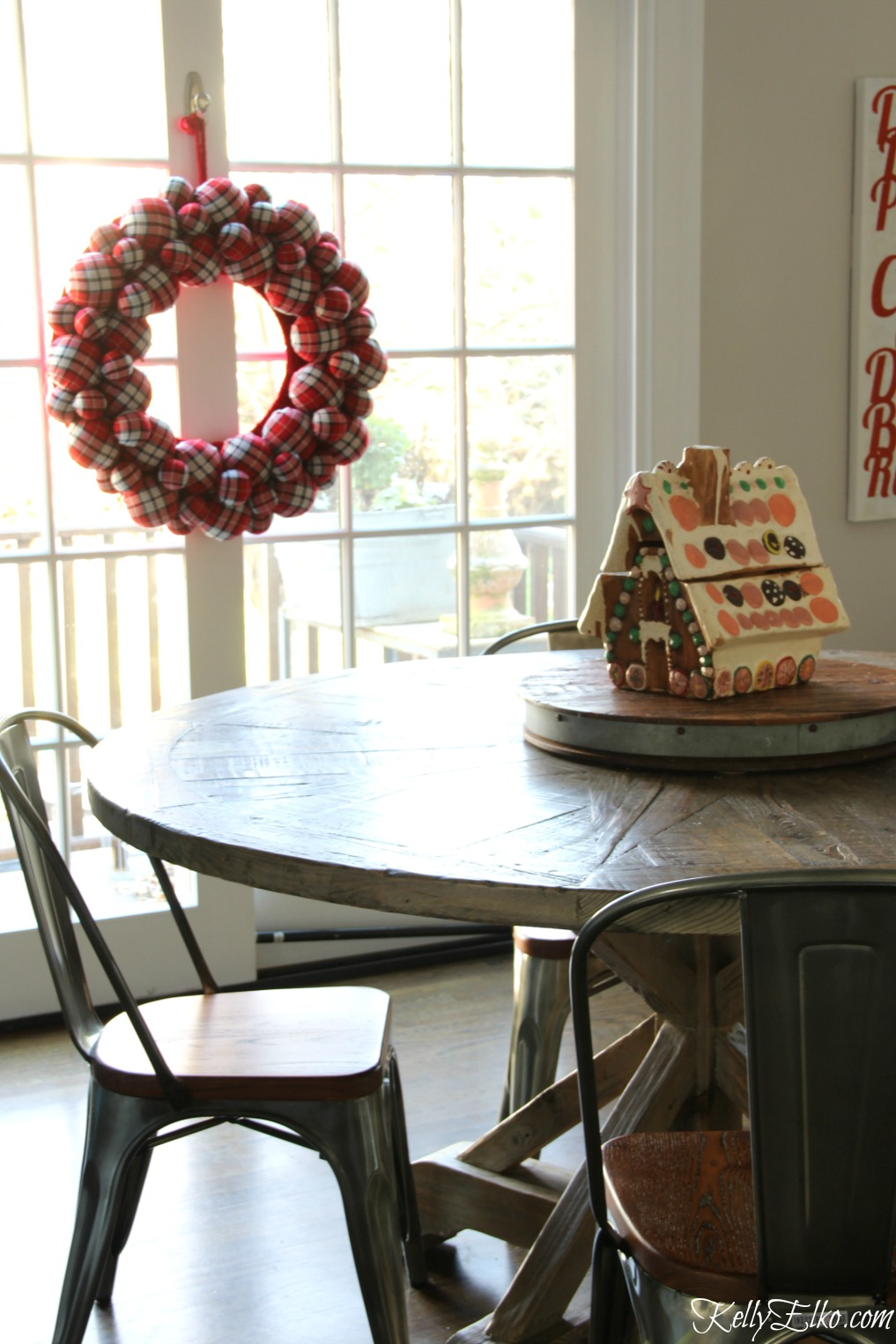 Christmas Kitchen - love this farmhouse table and chairs with giant plaid wreath kellyelko.com
