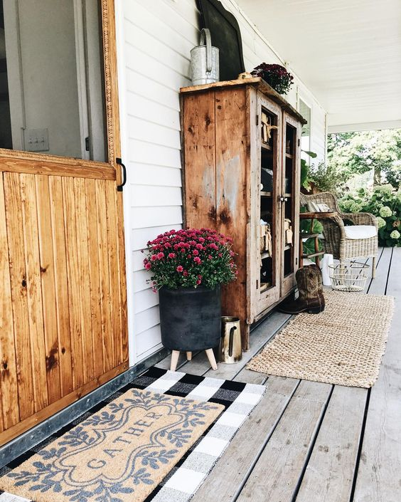 Farmhouse tour - love the porch with wood cabinet and wicker chair