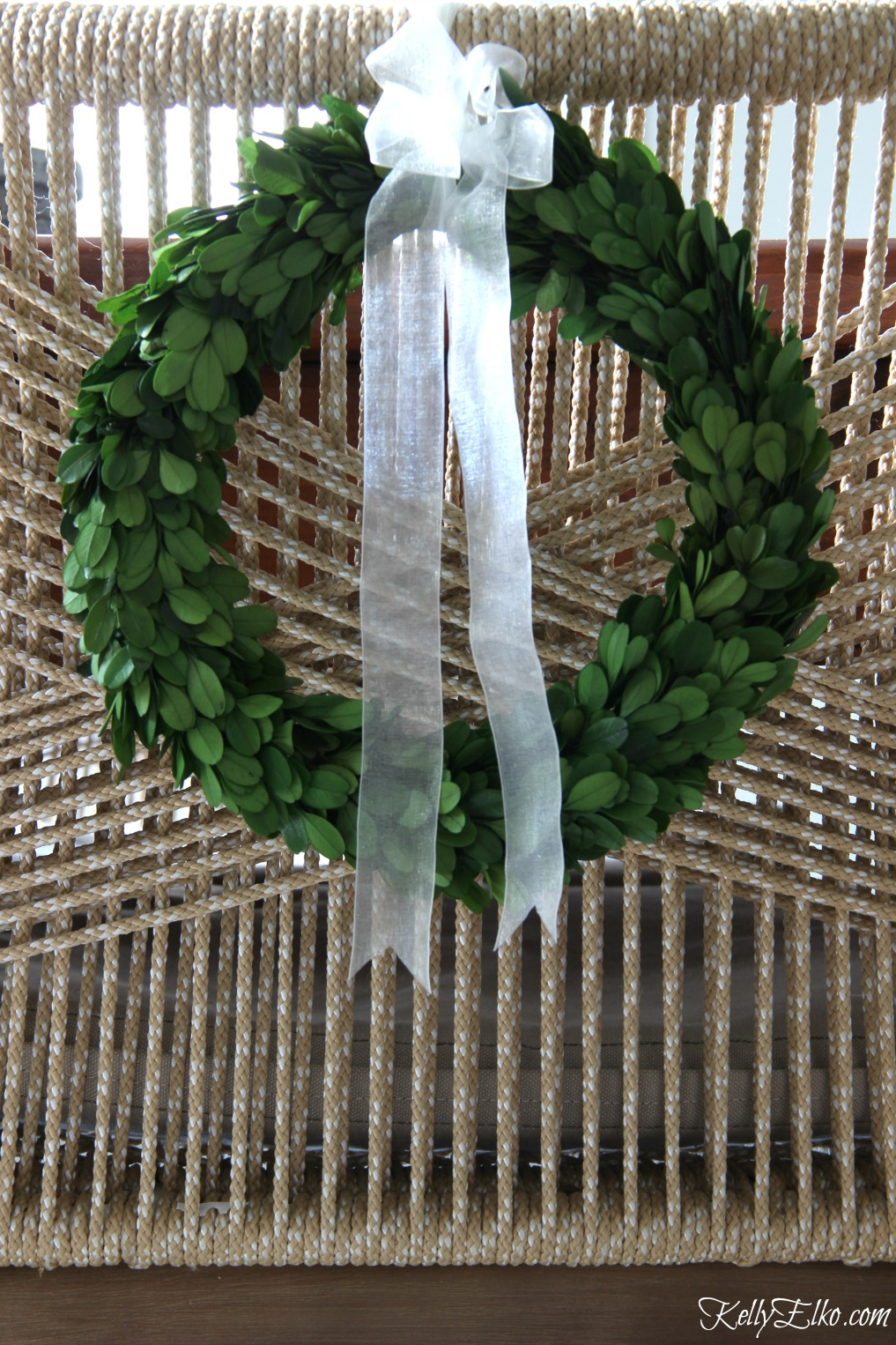 Tie preserved boxwood wreaths on back of chairs for the holidays kellyelko.com