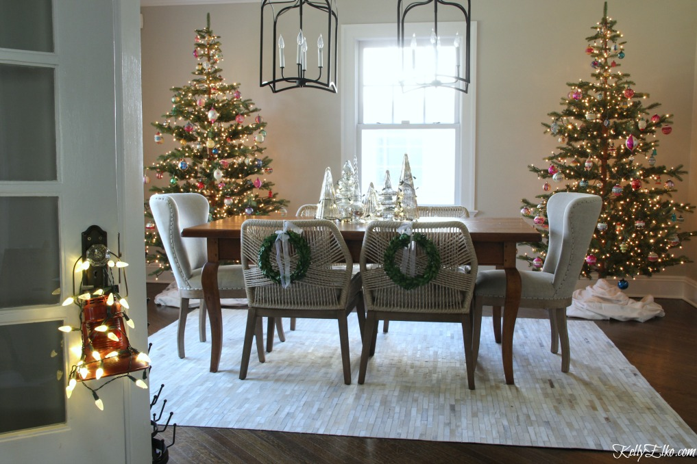Love this pair of faux fir Christmas trees in the dining room kellyelko.com