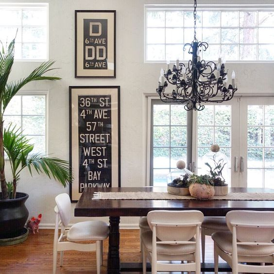 Beautiful dining room with mid century chairs, iron chandelier and NY subway art