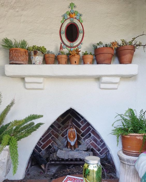 Outdoor fireplace with cute collection of plants in terra cotta pots