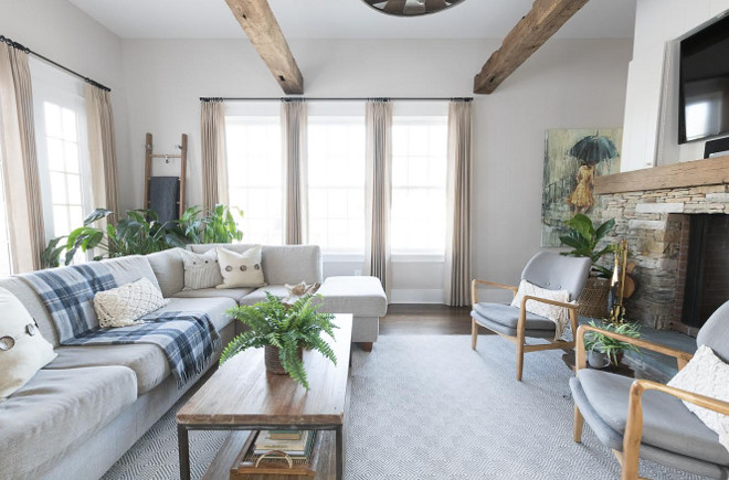 Eclectic Home Tour of Green Spruce Designs - love the warm gray paint, sectional sofa and antique wood ceiling beams in this cozy family room