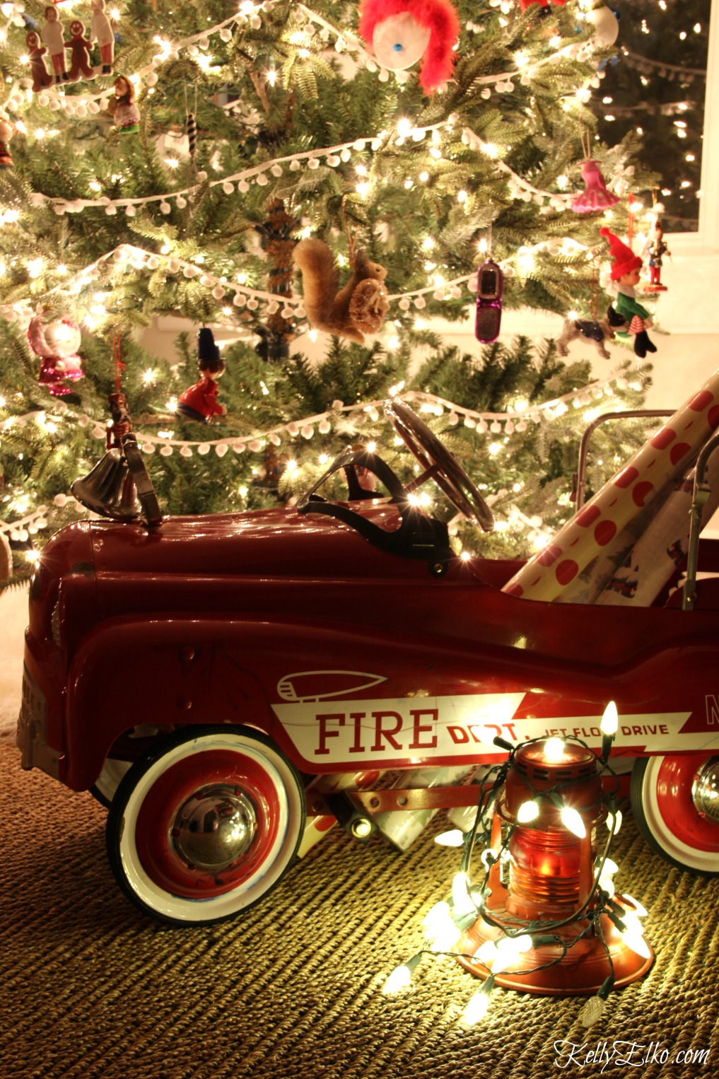 Christmas Nights Tour - see 25 of the best Christmas homes lit up at night! How fun is this cute little red fire truck filled with gift wrap kellyelko.com #christmas #christmasdecorating #christmasdecor #christmaslights