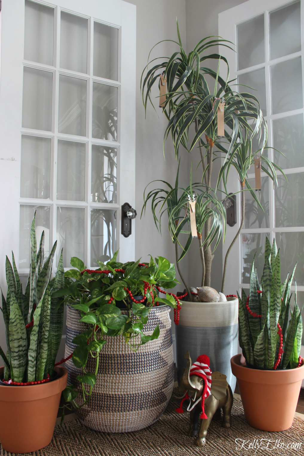 Simple Christmas decorating ideas - love the garland and ornaments in these everyday plants kellyelko.com